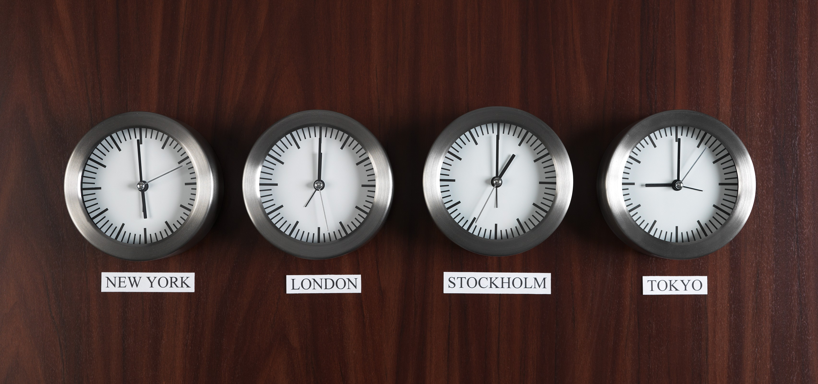 Four clocks with different time on Teak background